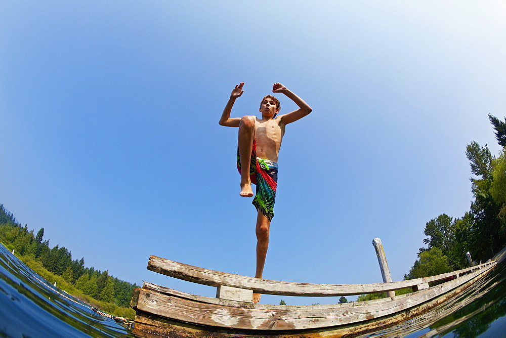 Boy jumping off dock into sunny lake