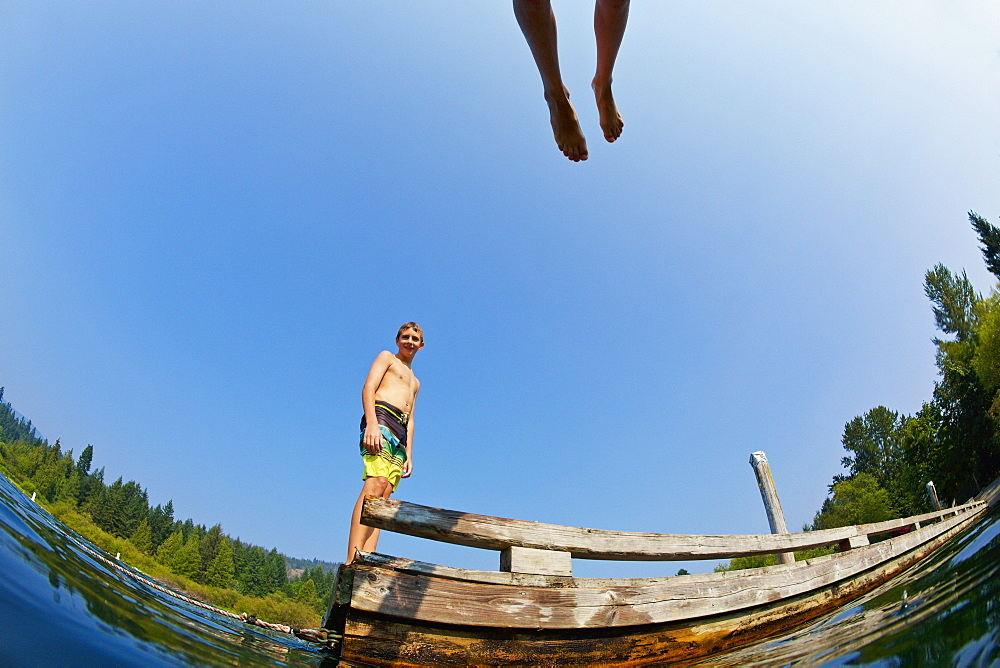 Boys jumping of dock into sunny summer lake