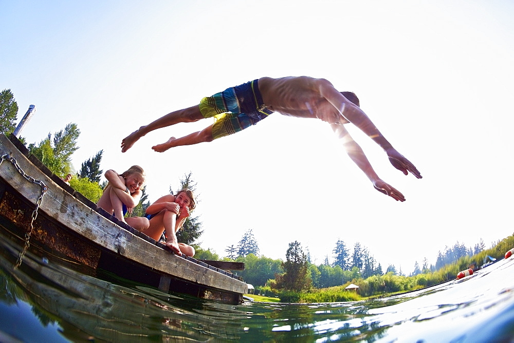 Boy jumping off dock into sunny summer lake