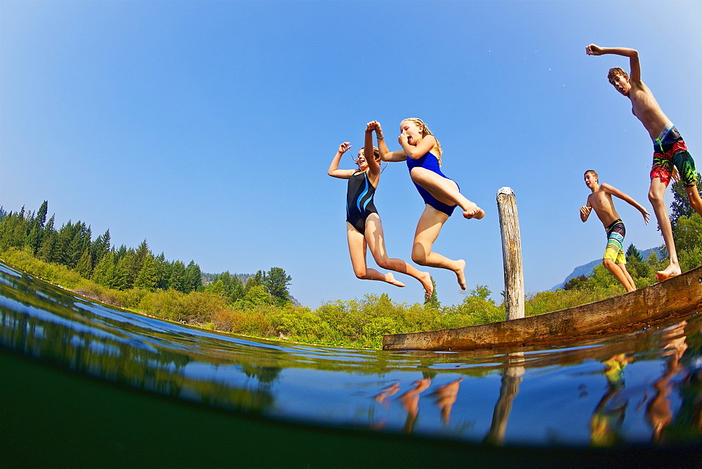 Kids jumping into sunny summer lake