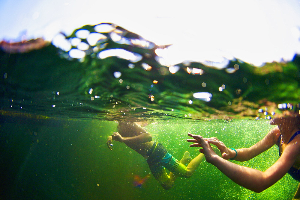 Underwater view of kids swimming in lake