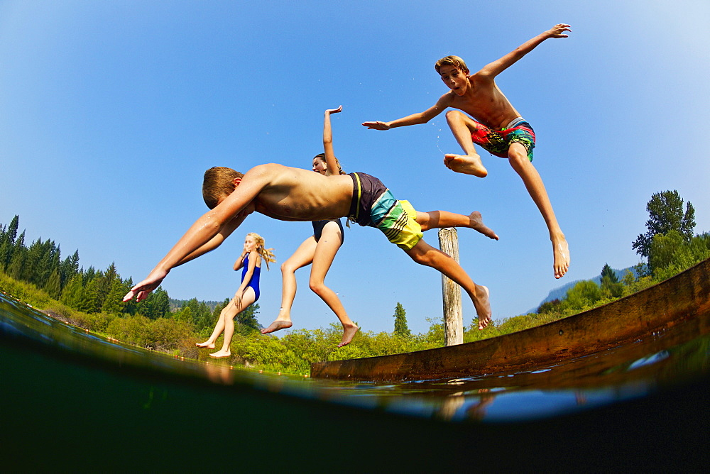 Playful kids jumping off dock into sunny summer lake