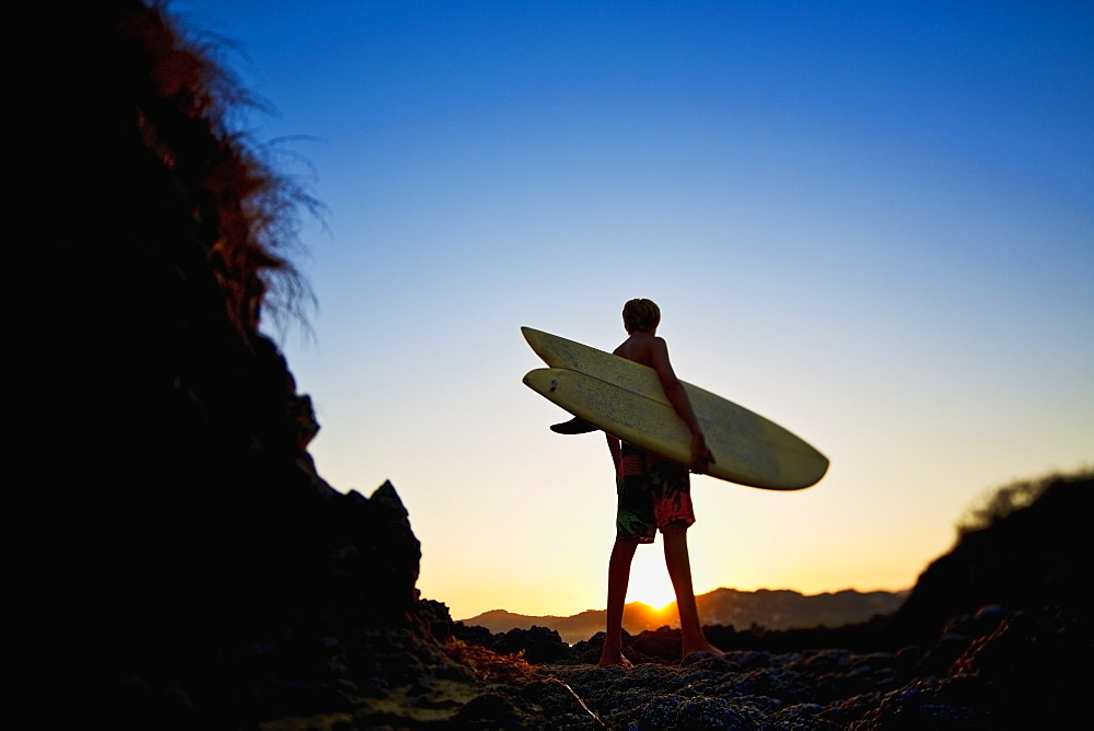 Silhouette boy with surfboard on idyllic beach at sunset