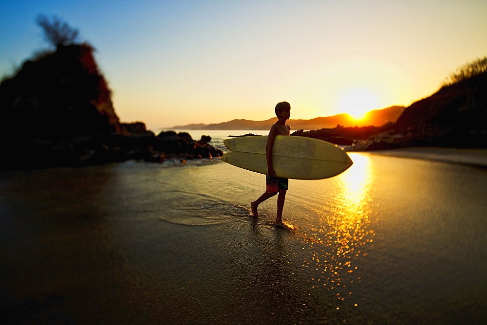 Silhouette boy with surfboard walking on idyllic ocean beach, Sayulita, Nayarit, Mexico
