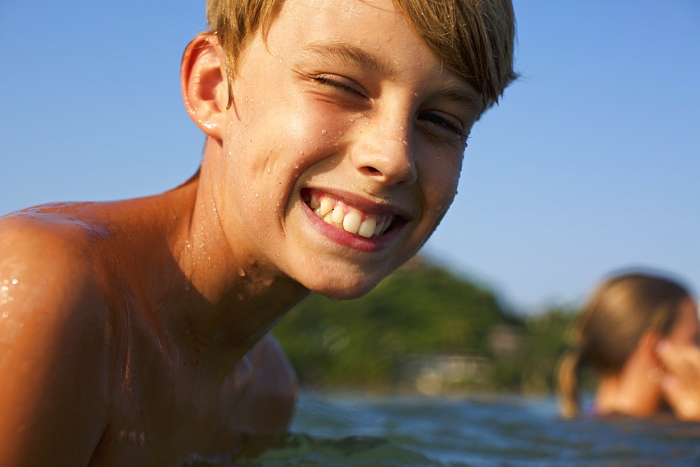 Portrait happy, carefree boy swimming in lake