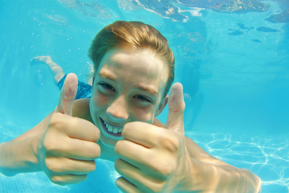 Portrait happy, carefree boy swimming underwater in swimming pool, gesturing thumbs up