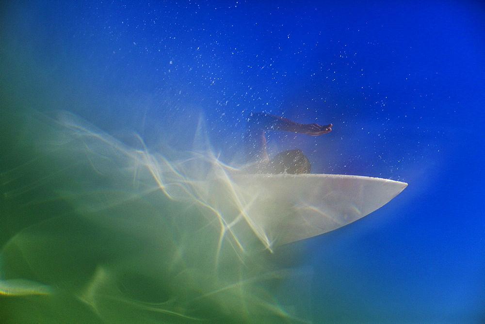 Underwater view of female surfer paddling out on surfboard