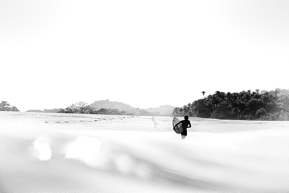 Surfer carrying surfboard into sunny ocean, San Pancho, Nayarit, Mexico