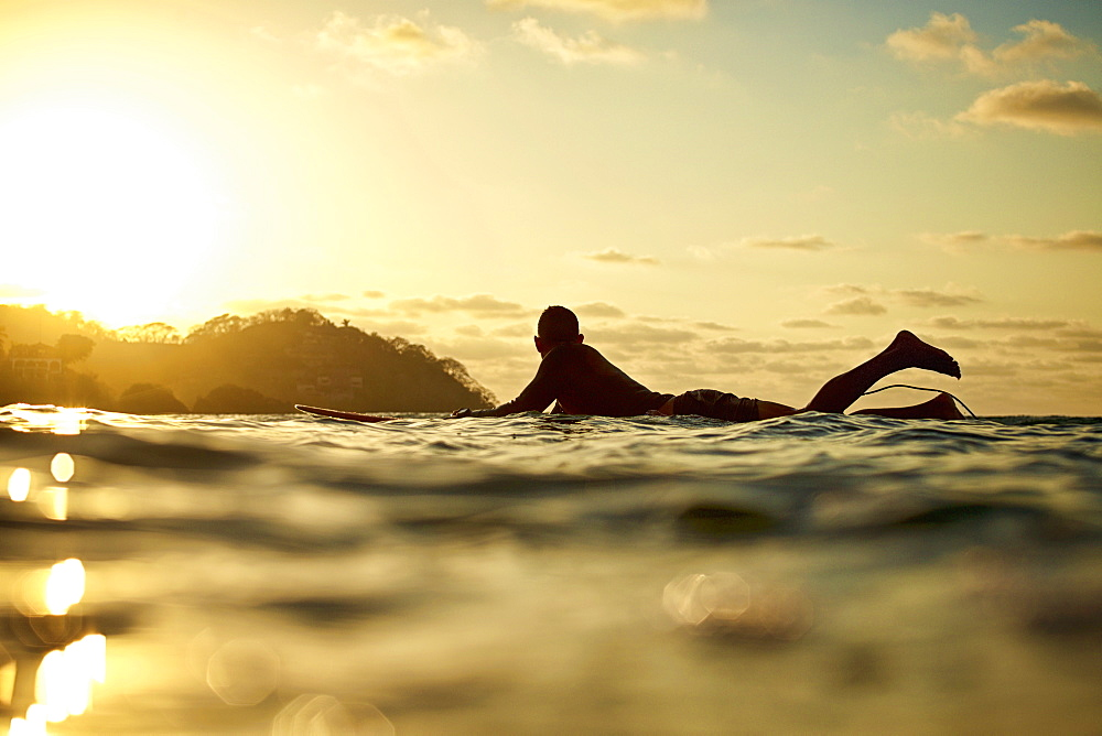Male surfer laying on surfboard on sunny ocean at sunset, Sayulita, Nayarit, Mexico