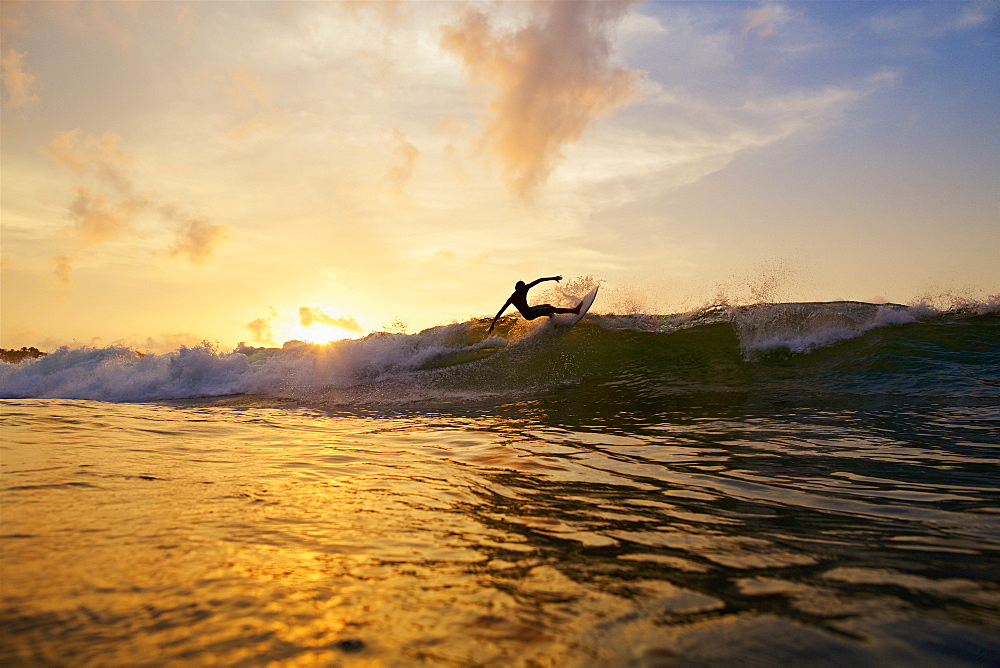 Male surfer making a turn off top of wave on sunset ocean, Sayulita, Nayarit, Mexico