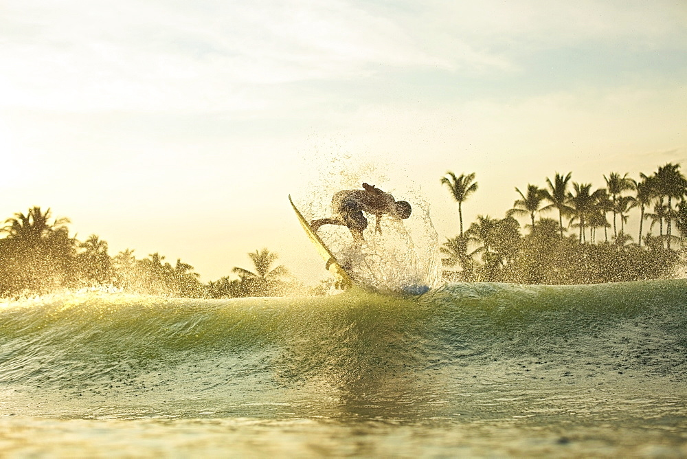 Male surfer catching air behind ocean wave at sunrise, Sayulita, Nayarit, Mexico