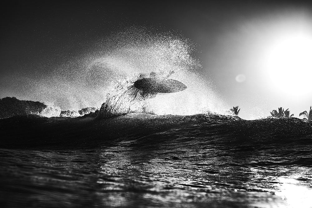 Surfer catching air behind ocean wave at sunrise, Sayulita, Nayarit, Mexico