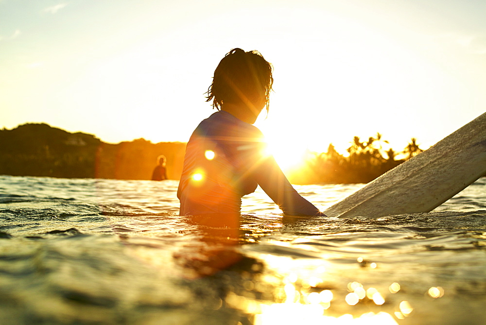 Female surfer on surfboard on sunny ocean at sunrise, Sayulita, Nayarit, Mexico