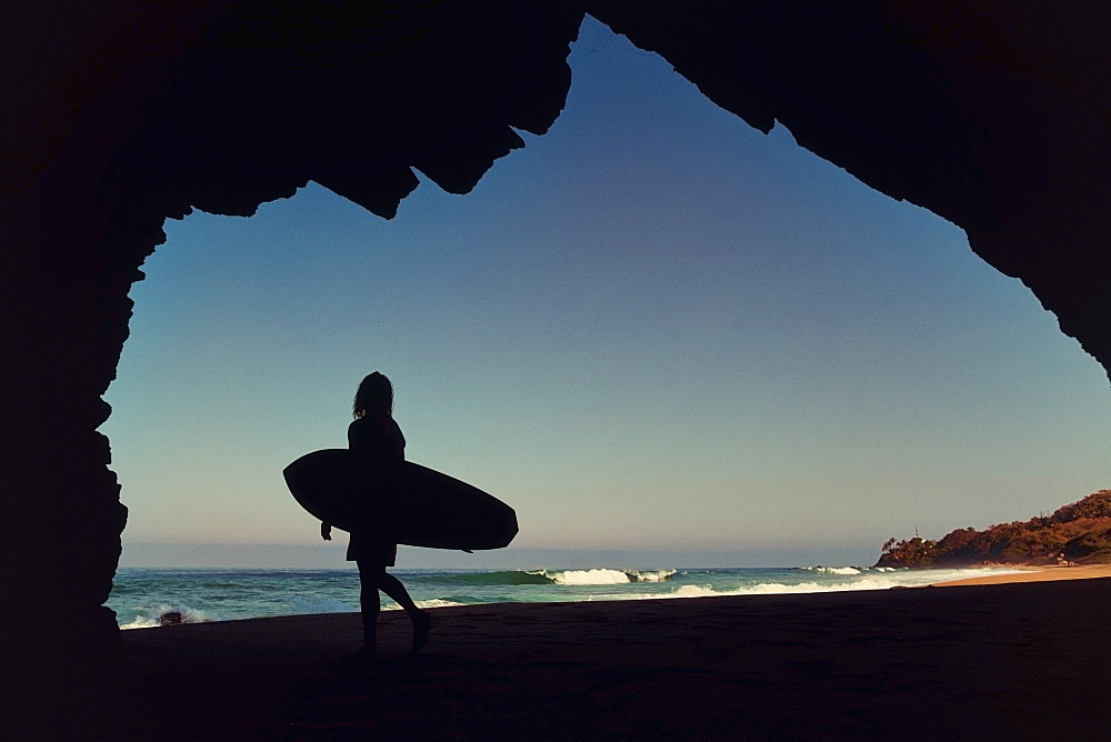 Silhouette female surfer in cave on sunny ocean beach, Sayulita, Nayarit, Mexico