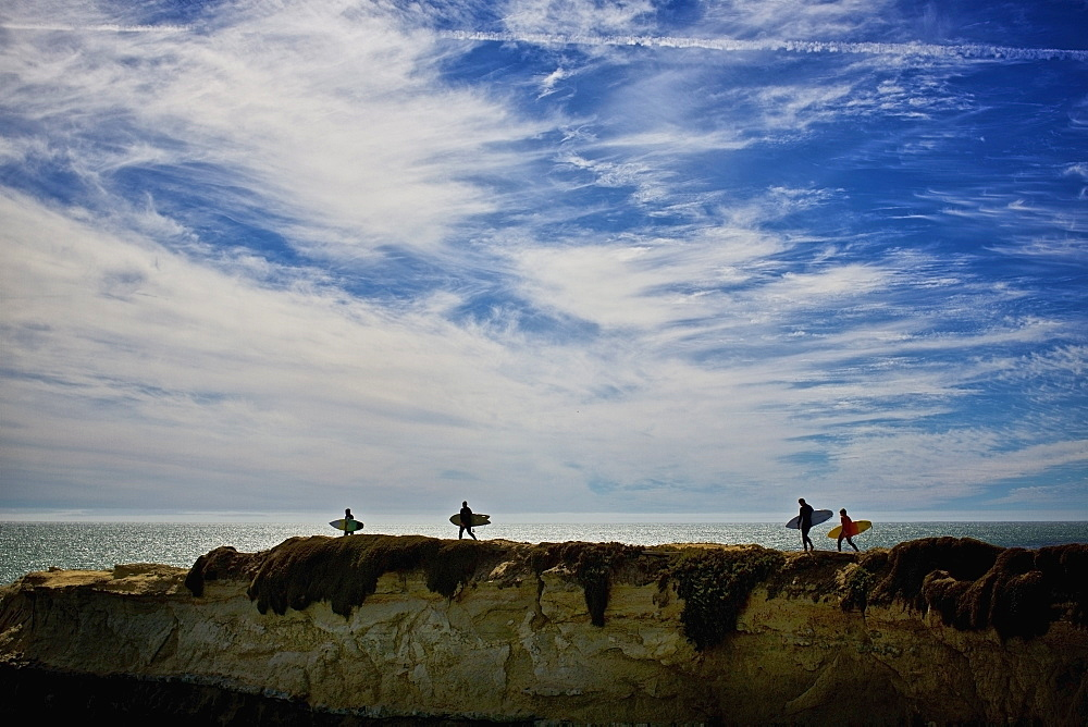 Surfers carrying surfboards on ocean rocks, Santa Cruz, California, USA