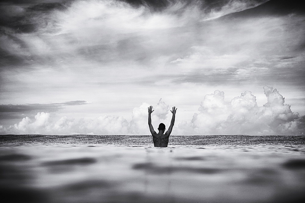 Surfer stretching arms overhead in ocean, San Pancho, Nayarit, Mexico