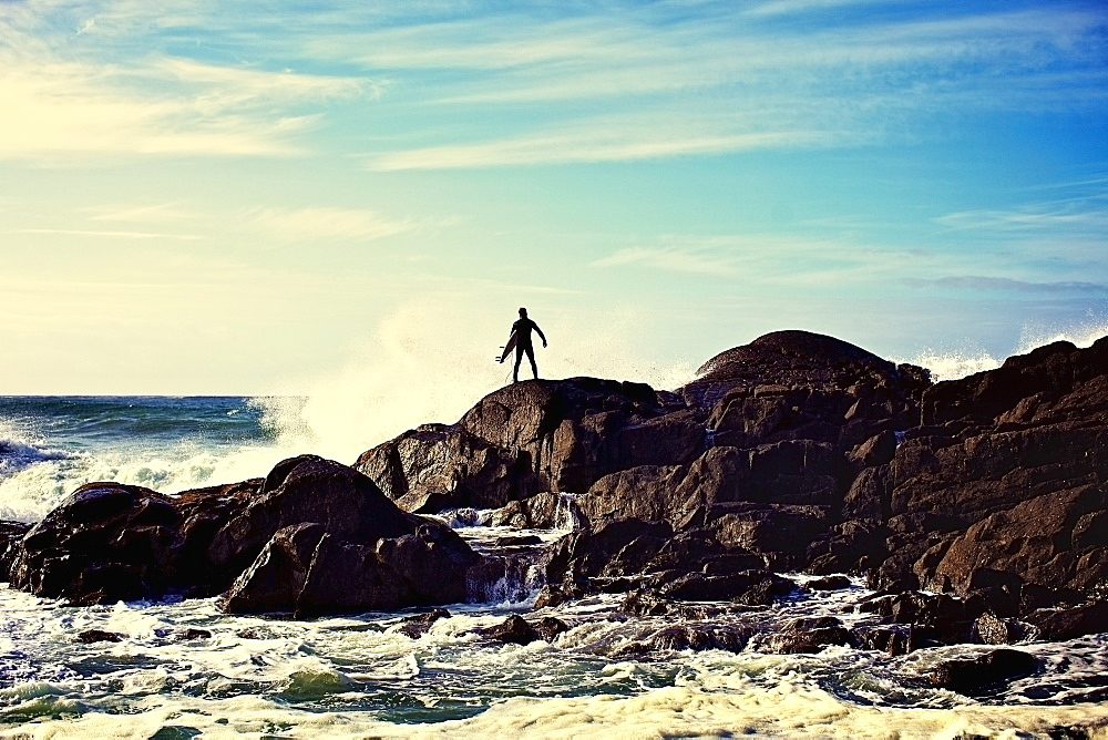 Silhouette male surfer watching ocean waves crash against rocks on sunny beach, Tofino, Canada