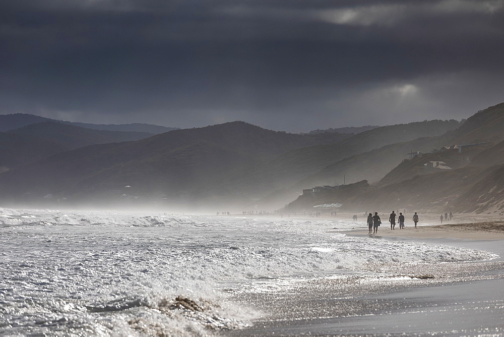 Ominous clouds over silhouetted people walking on ocean beach, Aireys Inlet, Victoria, Australia