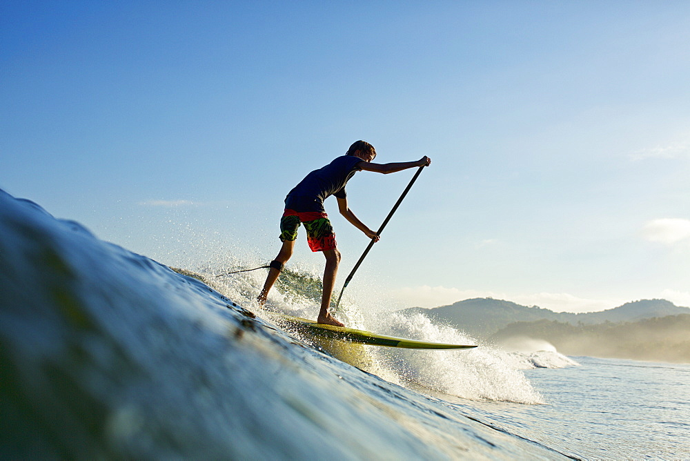 Boy paddleboarding over ocean wave, Sayulita, Nayarit, Mexico