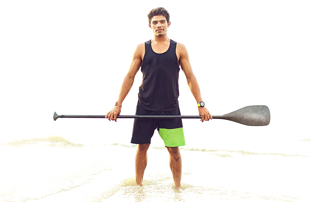 Portrait confident young man holding oar in ocean surf