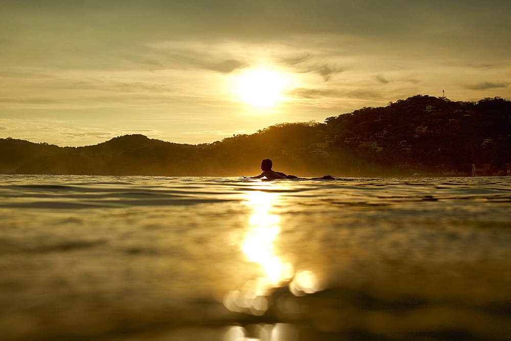 Silhouette young man laying on surfboard on tranquil sunset ocean, Sayulita, Nayarit, Mexico