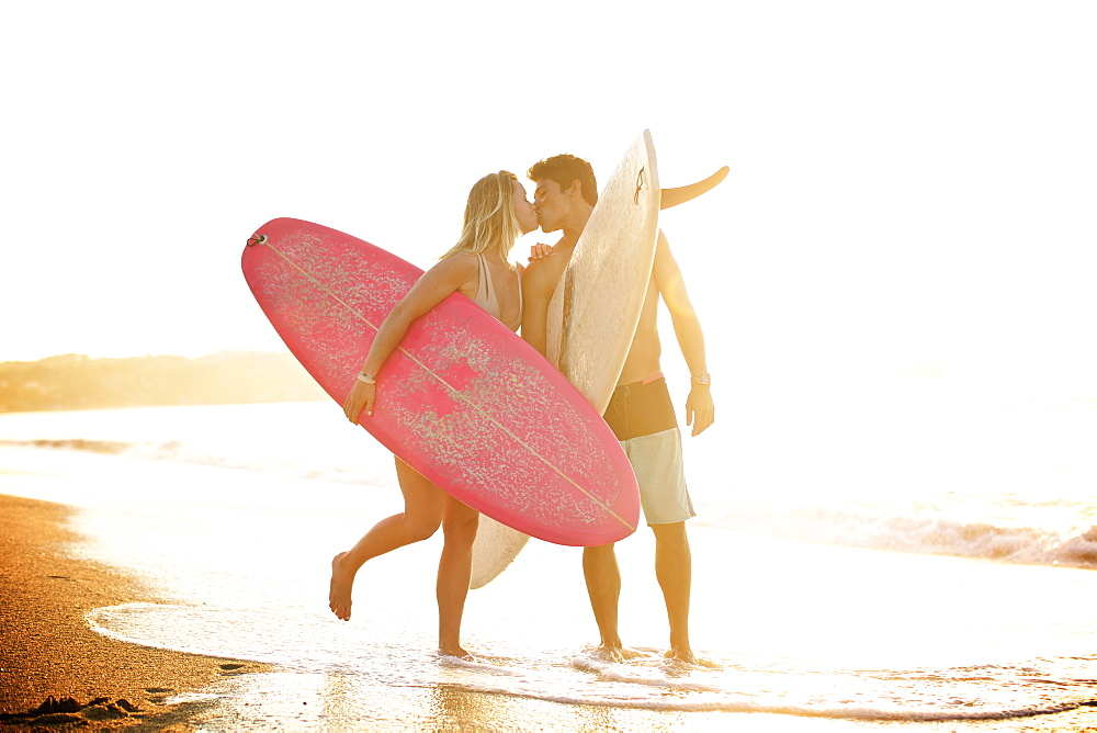 Young, affectionate couple with surfboards kissing on sunny ocean beach