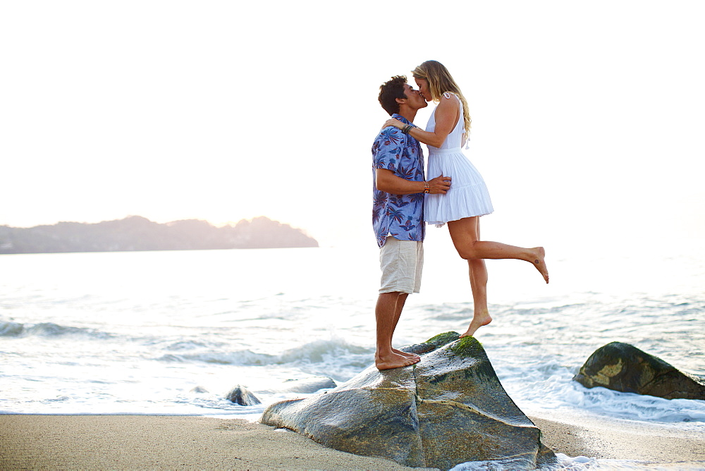 Affectionate, romantic young couple kissing on ocean rock, Sayulita, Nayarit, Mexico
