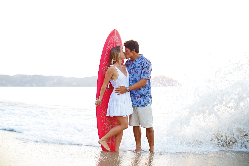 Affectionate couple with surfboard kissing on ocean beach, Sayulita, Nayarit, Mexico