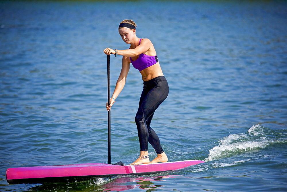 Young woman paddleboarding on sunny ocean