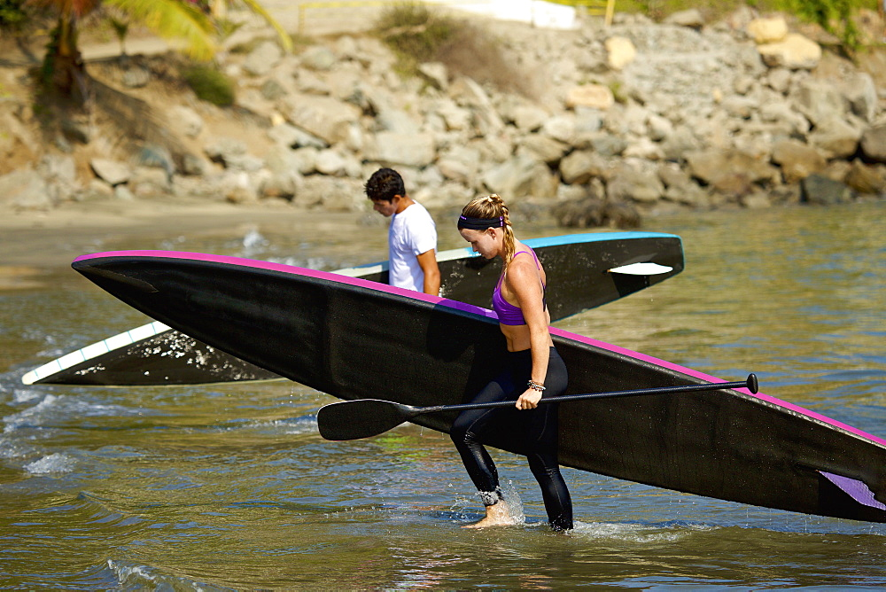 Young couple with paddleboards wading in ocean