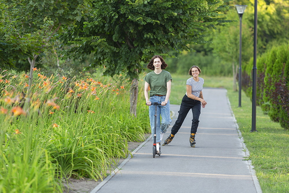 Women rollerblading and riding push scooter on park footpath