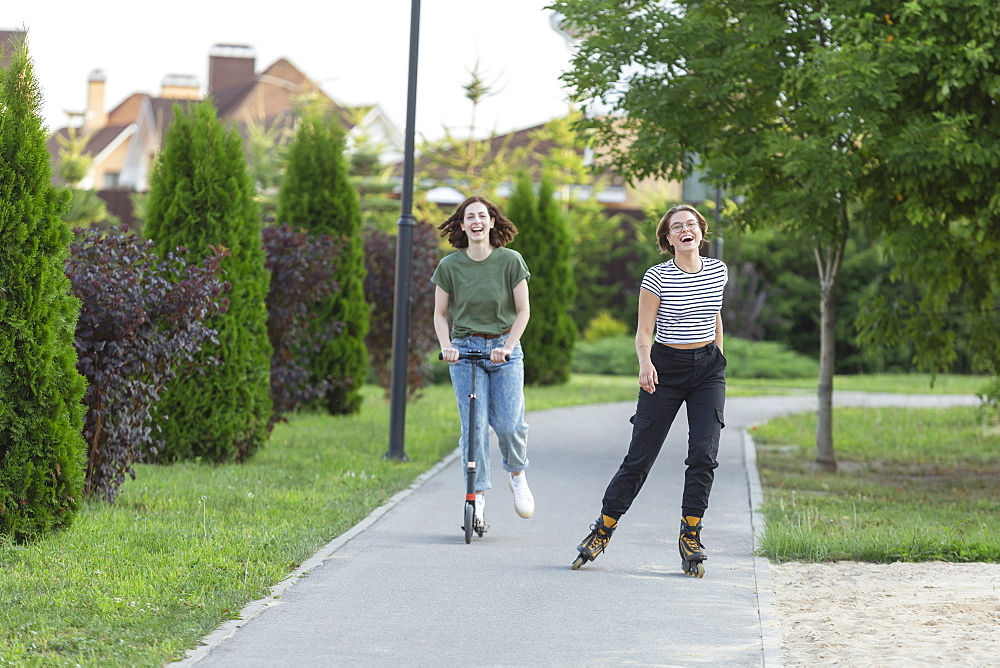 Happy women friends rollerblading and riding push scooter on sidewalk