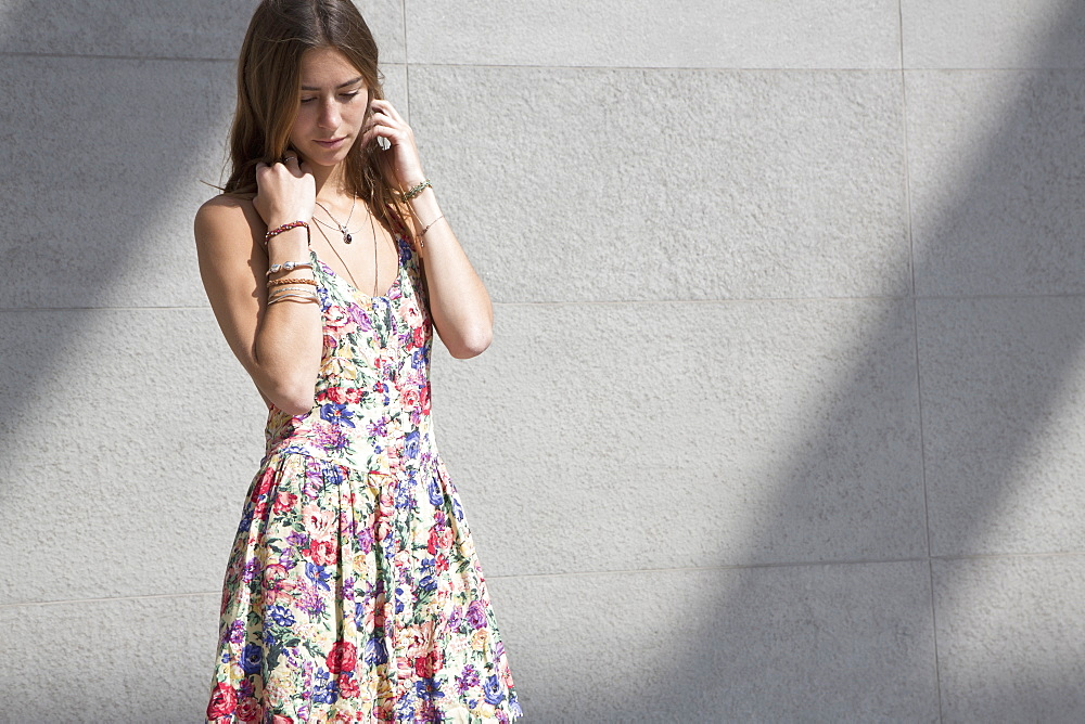 Young woman standing beside wall, looking down