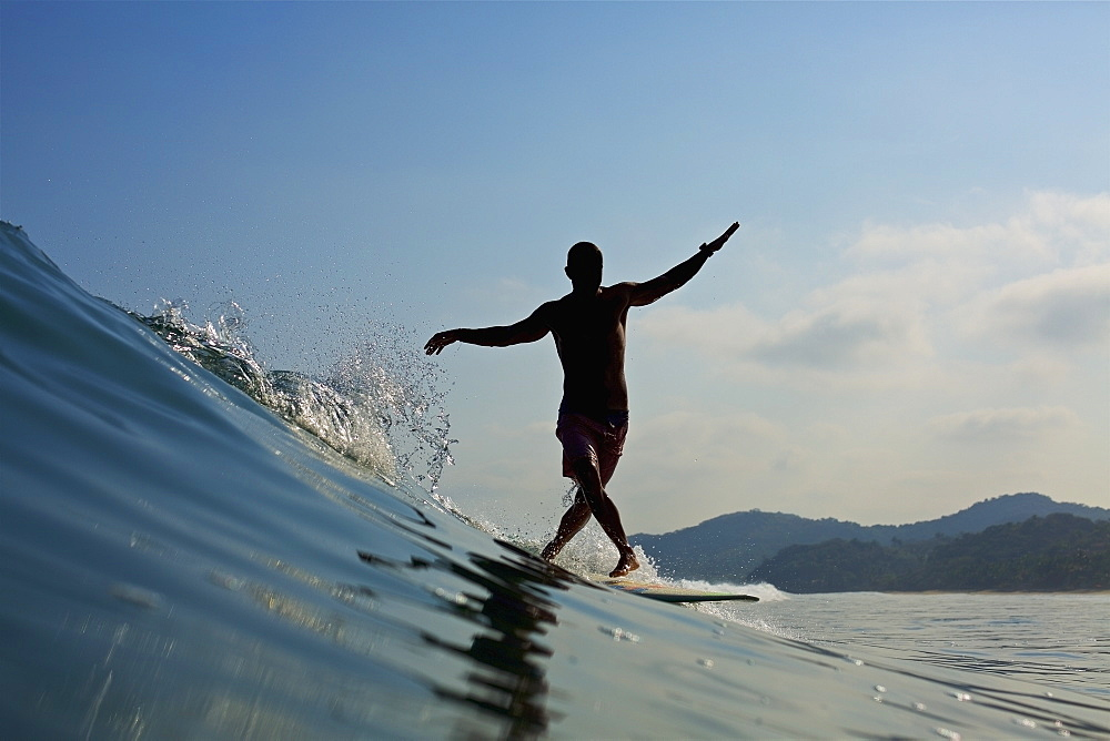 Male surfer balancing on surfboard, riding ocean wave