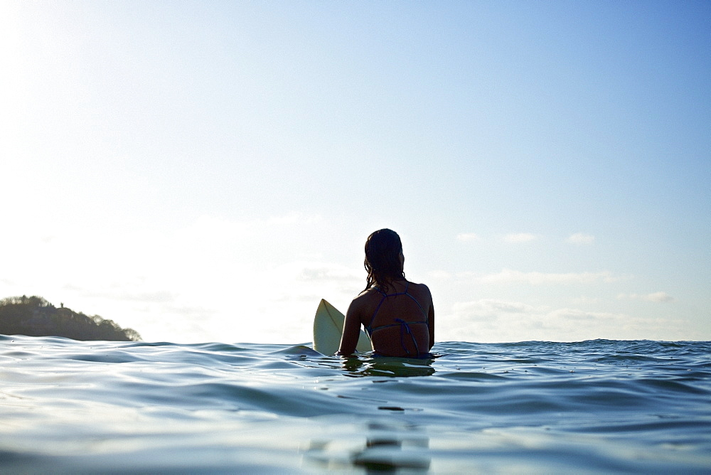 Silhouette female surfer straddling surfboard, waiting in sunny blue ocean