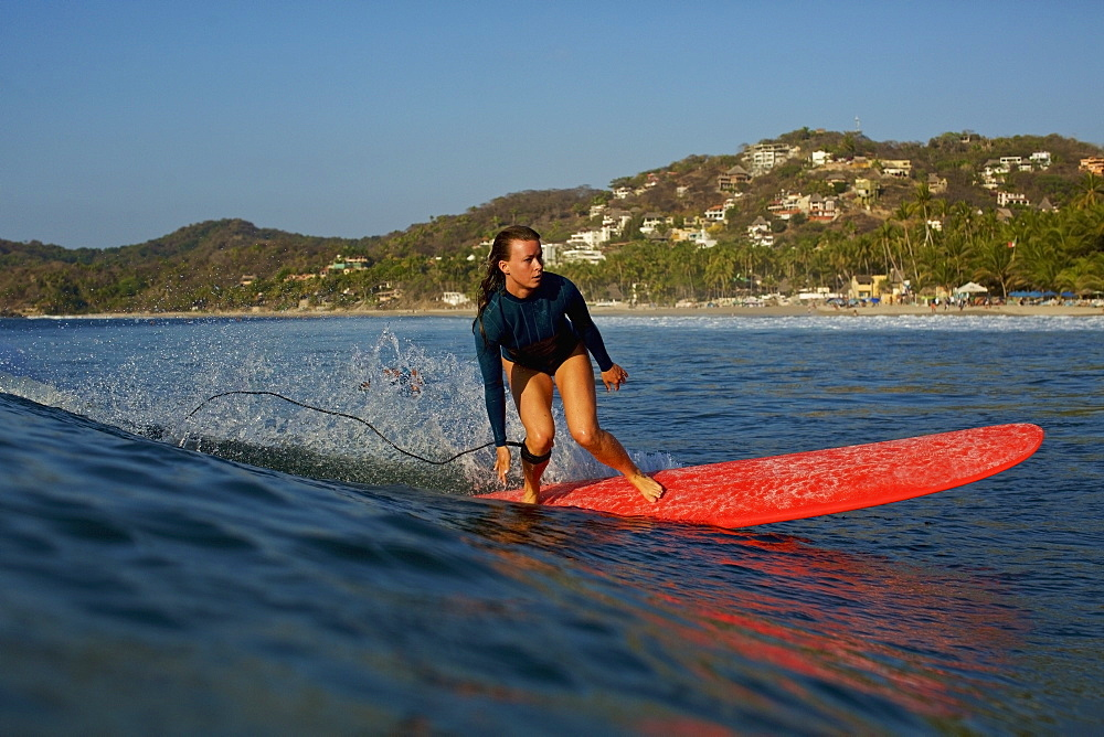 Female surfer riding ocean wave, Sayulita, Nayarit, Mexico