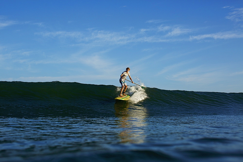 Boy paddle boarder riding sunny, blue ocean wave