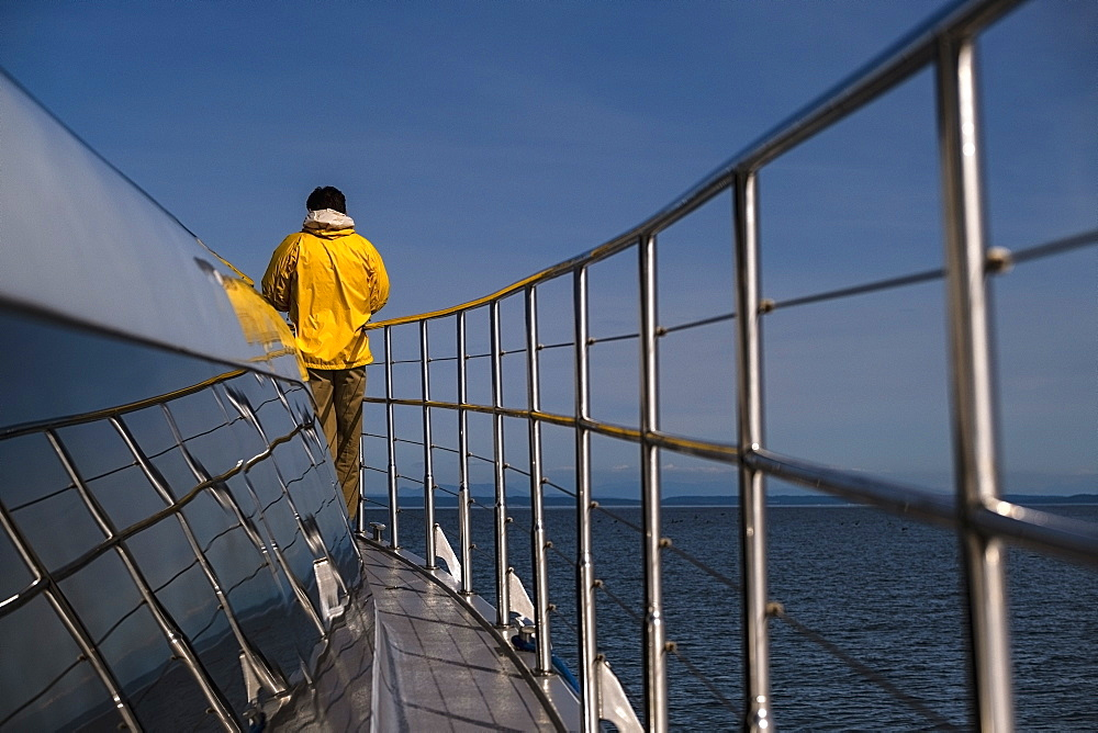 Man standing on deck of boat on sunny ocean