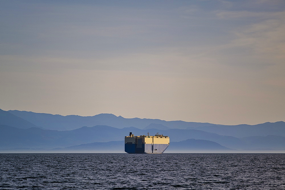Container ship on sunny, idyllic ocean with Olympic Mountain Range in background