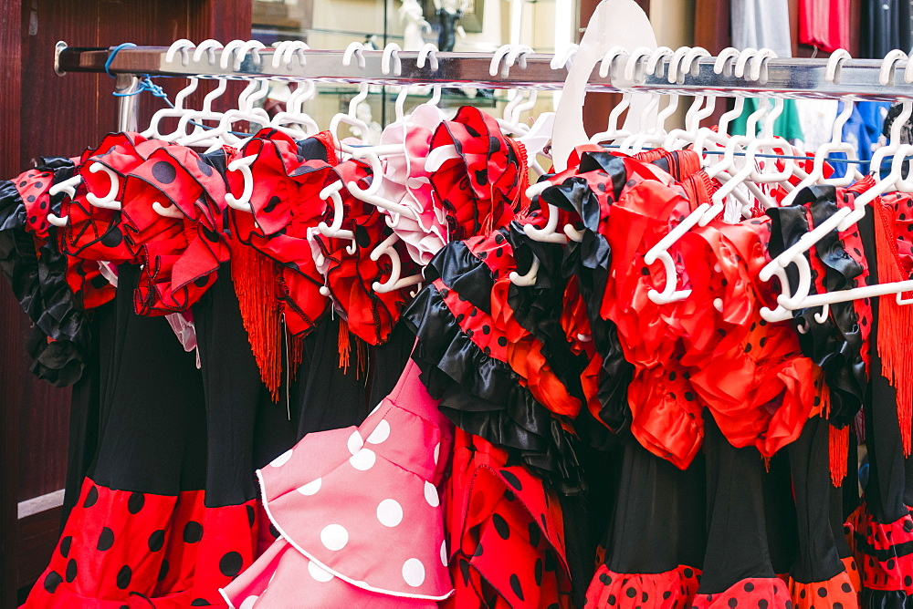 Red and black polka-dot costume dresses hanging on clothes rack in shop