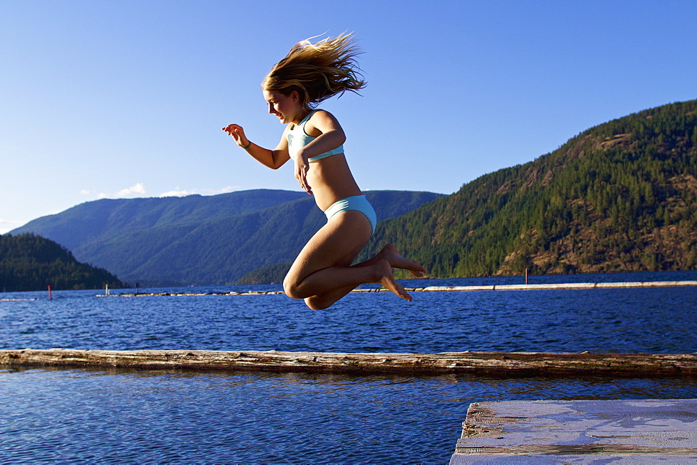 Carefree girl jumping off dock into sunny lake, Lake Cowichan, British Columbia, Canada