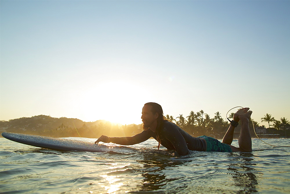 Male surfer paddling out on sunset ocean, Sayulita, Nayarit, Mexico