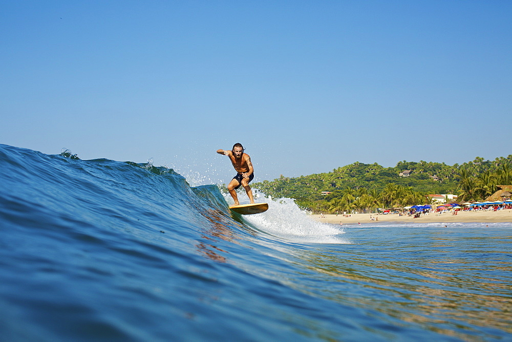 Male surfer riding wave, Sayulita, Nayarit, Mexico