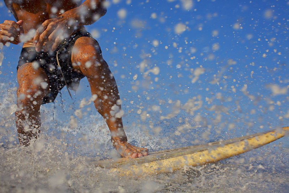 Male surfer riding ocean wave, splashing
