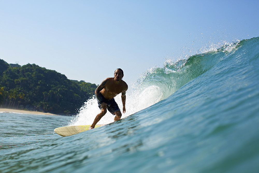 Male surfer riding sunny ocean wave