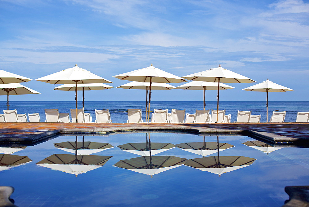 White beach umbrellas and lounge chairs at sunny ocean poolside, Punta de Mita, Nayarit, Mexico