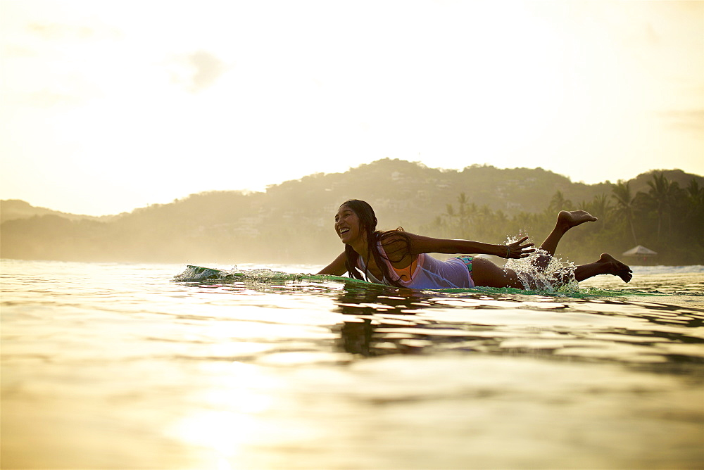 Happy female surfer paddling out in ocean on surfboard, Sayulita, Nayarit, Mexico - 1177-2758