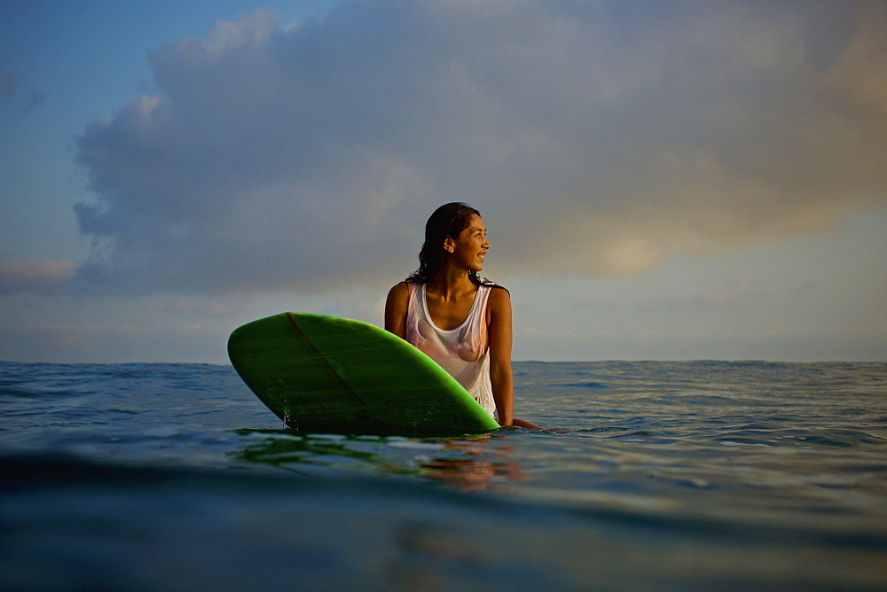 Female surfer waiting on surfboard in ocean