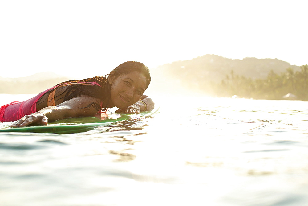Portrait confident, serene female surfer laying on surfboard in sunny ocean