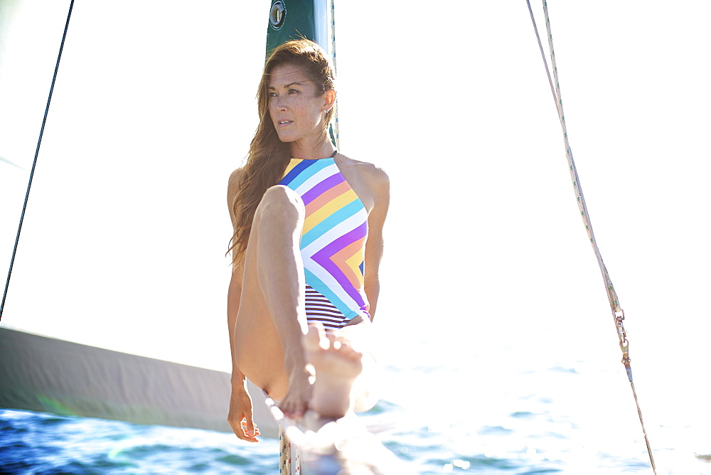 Confident woman in bathing suit on sunny sailboat